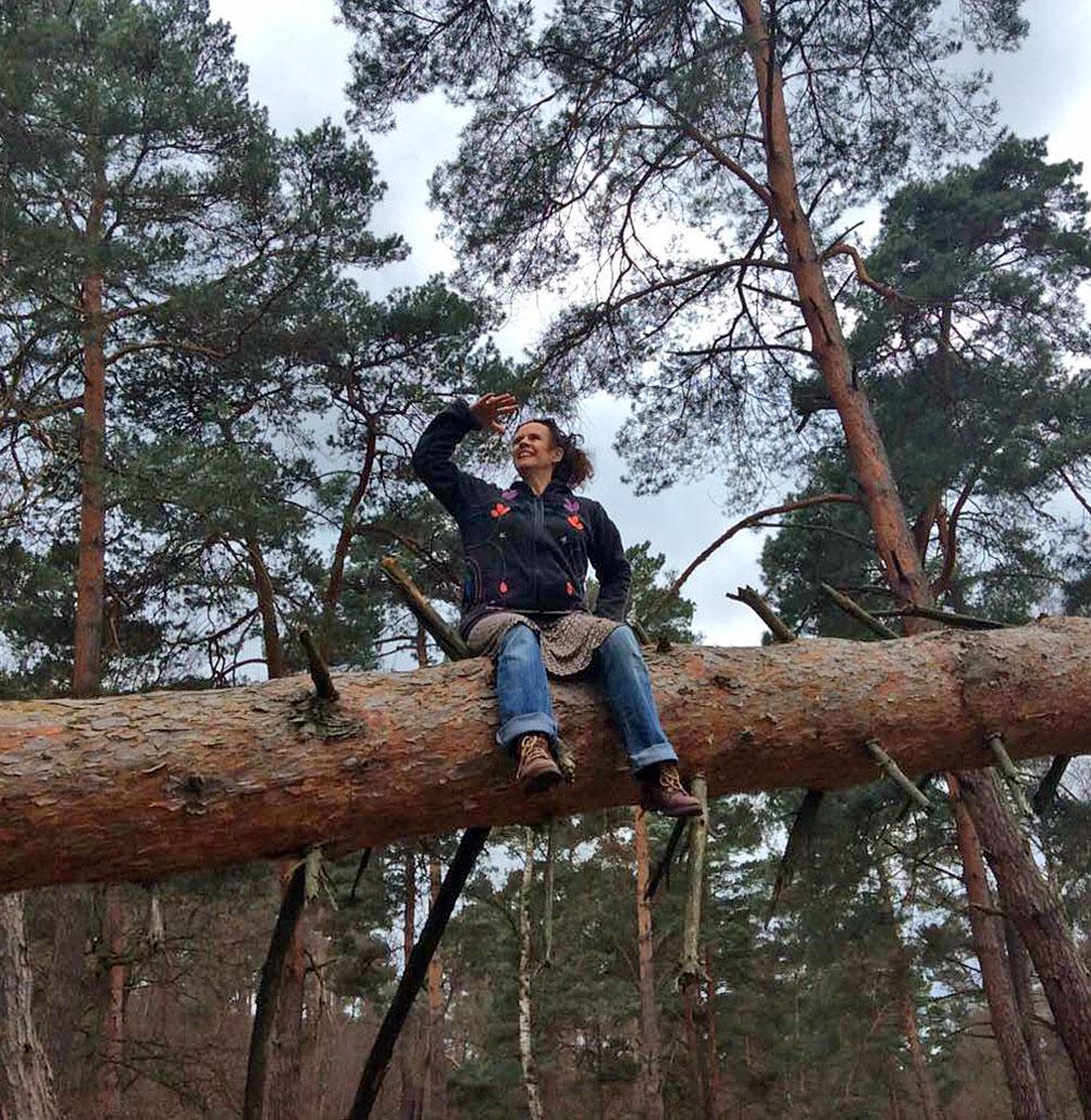 Nessi sitzt hoch auf einem umgefallenen Baum