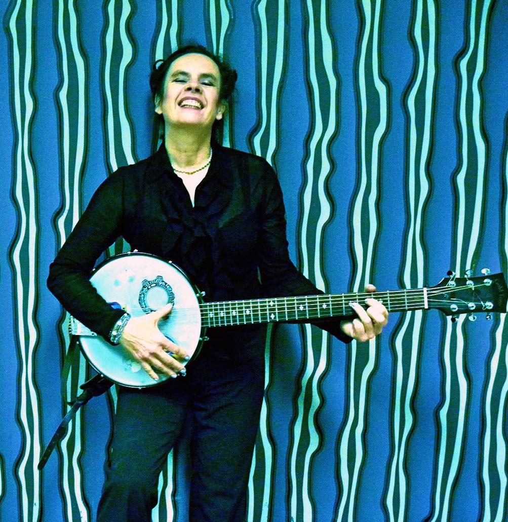 Nessi banjospielend vor Streifentapete